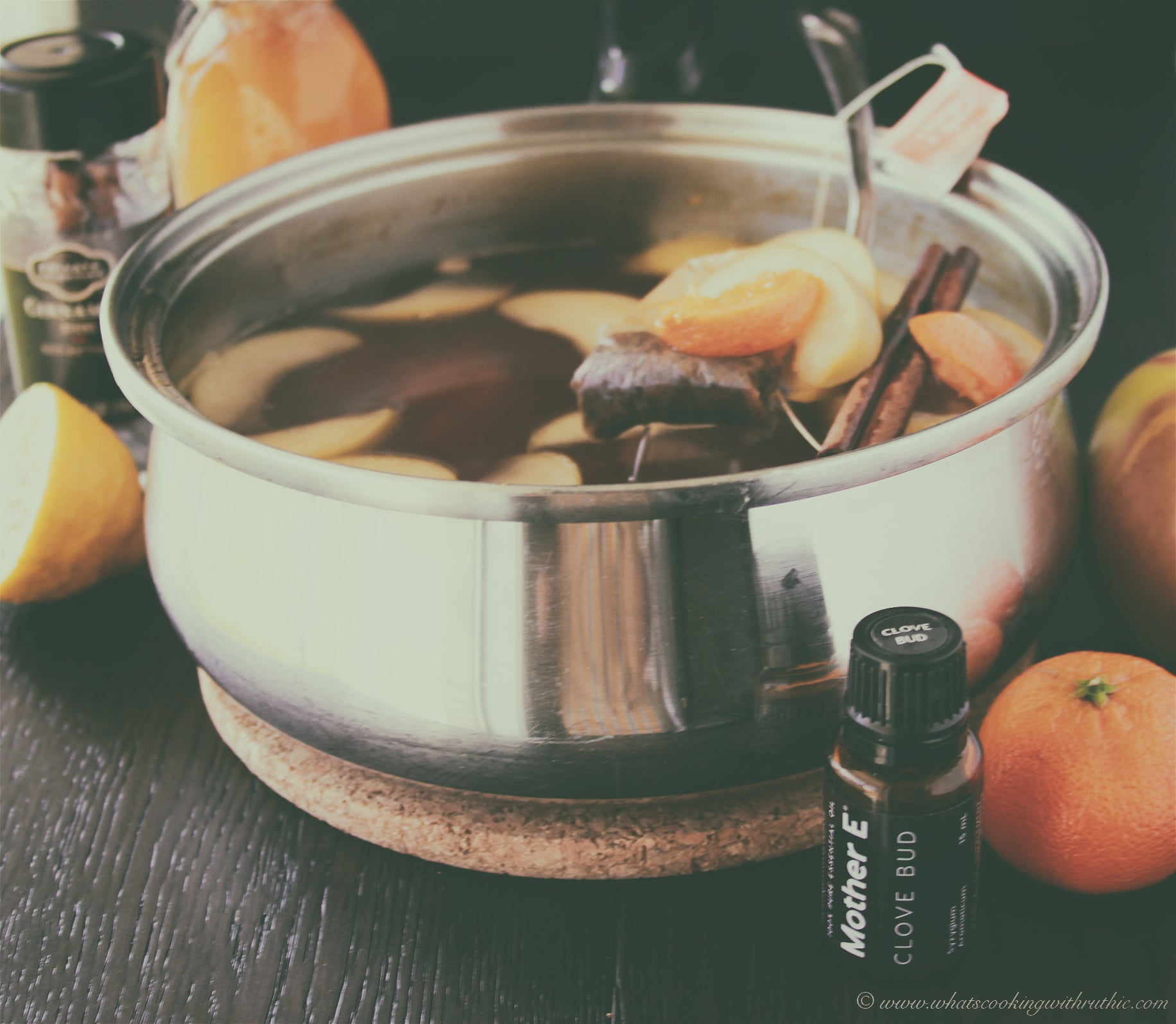 Clove Bud Essential Oil with pot of Orange Spice Wassail