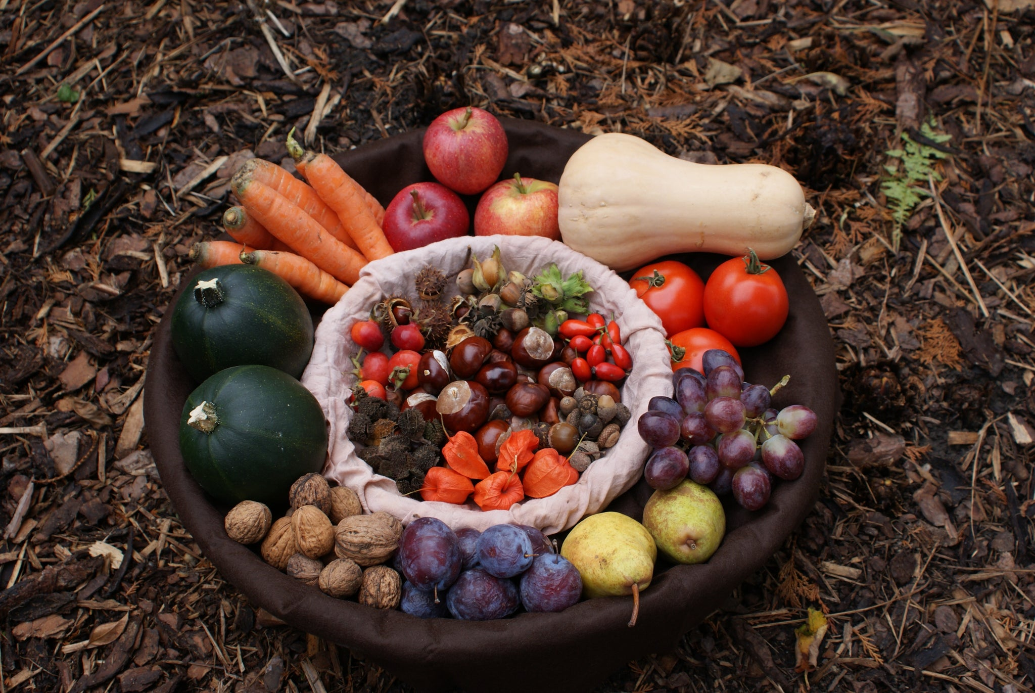 Thanksgiving harvest with vegetables, fruits, and nuts in a bowl on the earthy ground