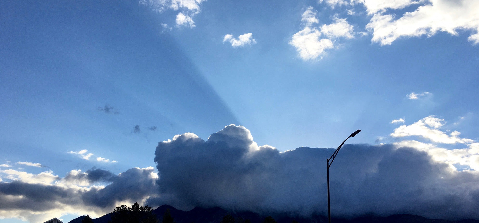 Blue Sky with sun rays, clouds, and lamp post