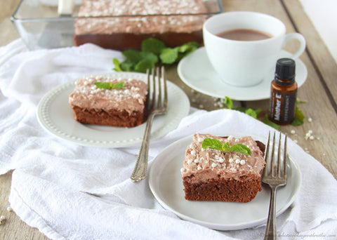 Two brownies on plates with forks, peppermint sprigs and pearl sprinkles as garnish, with hot chocolate and Mother E peppermint essential oil