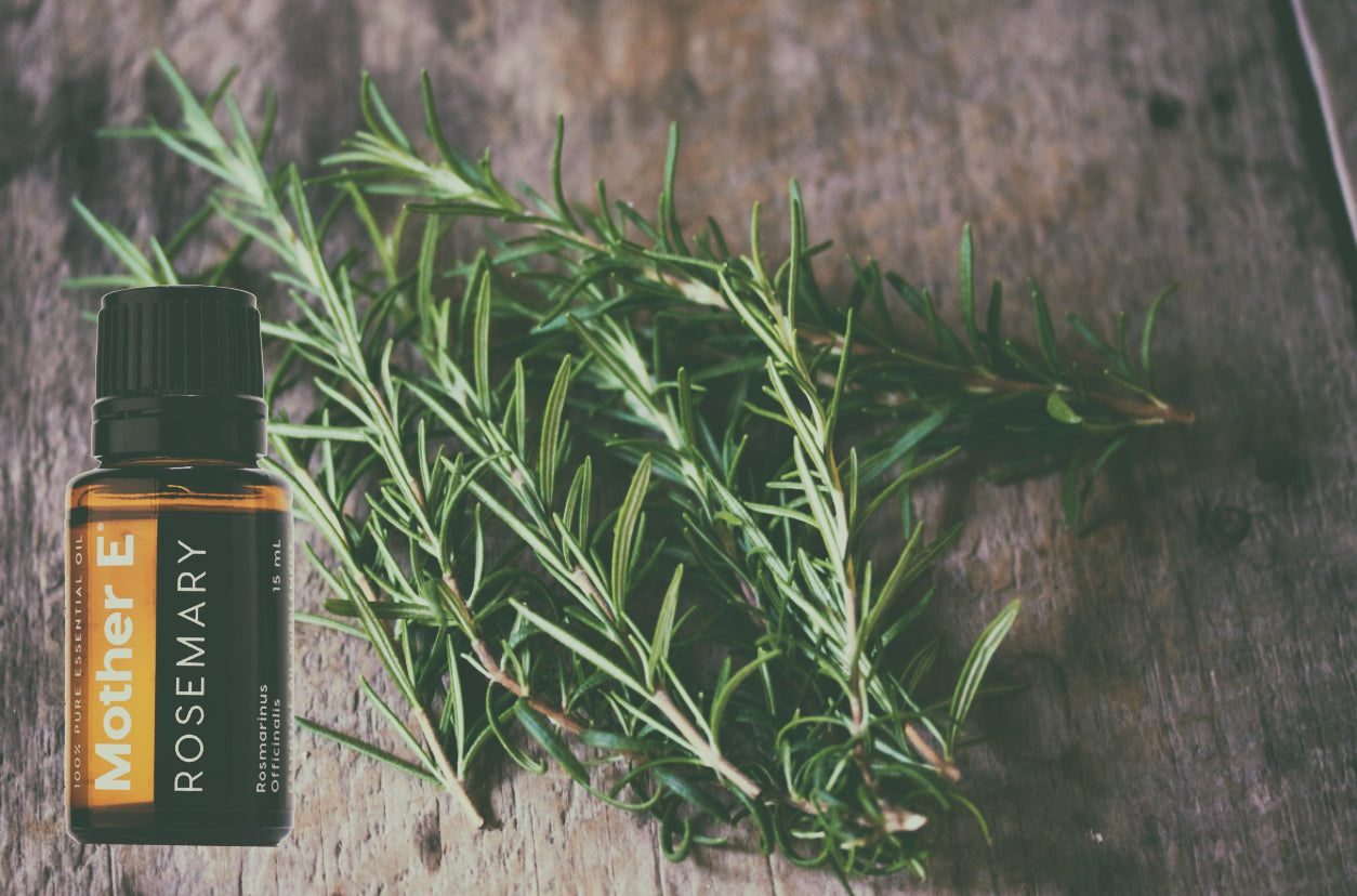 Rosemary Essential Oil Bottle with bundle of rosemary