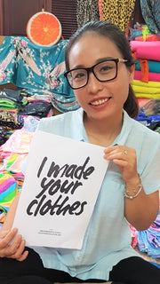 Vietnamese Tailor holding a poster which reads 'I made your clotes' sustainable fashion