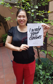 Fair Trade image. State of Disarray tailor Mrs Thuy holding a poster by Fashion Revolution