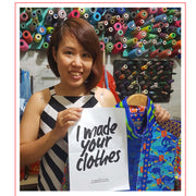 Mrs Linh A State of Disarray Tailor holding a Fashion Revolution poster.