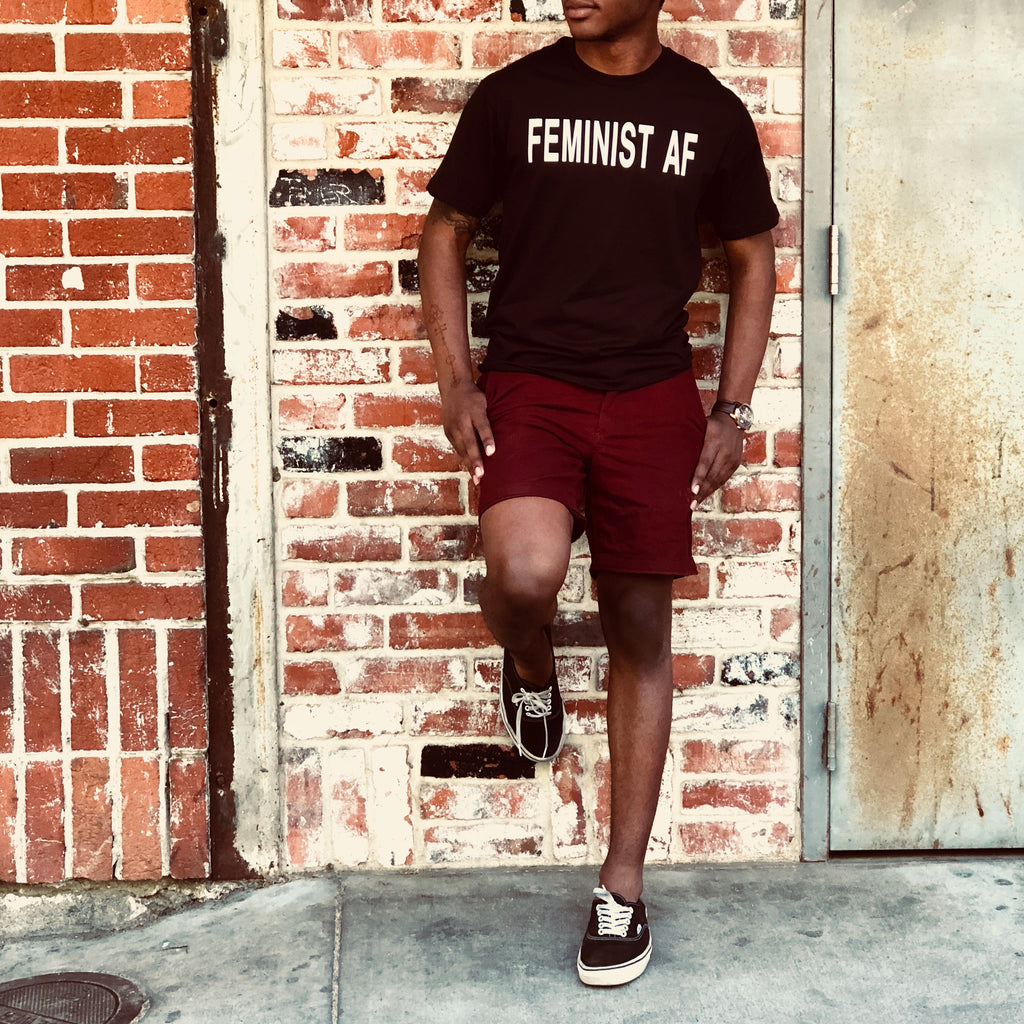 African American model in black feminist AF t-tee, leaning against brick wall, in vans