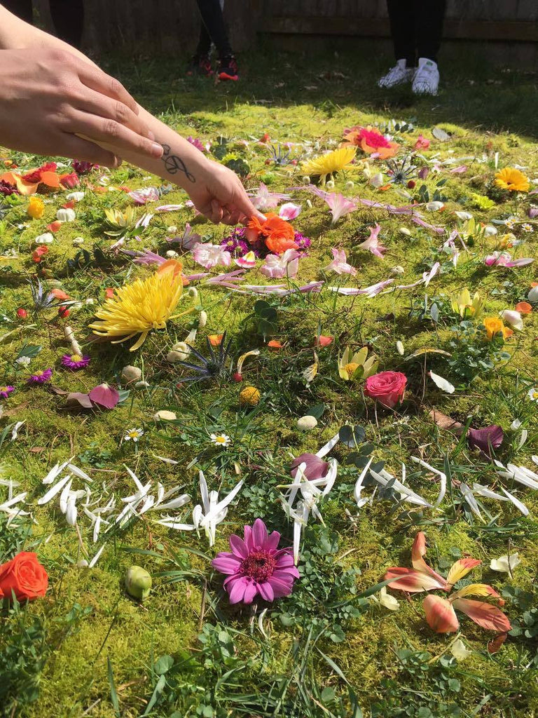 Woman places petals and blooms in a circular pattern for a flower mandala