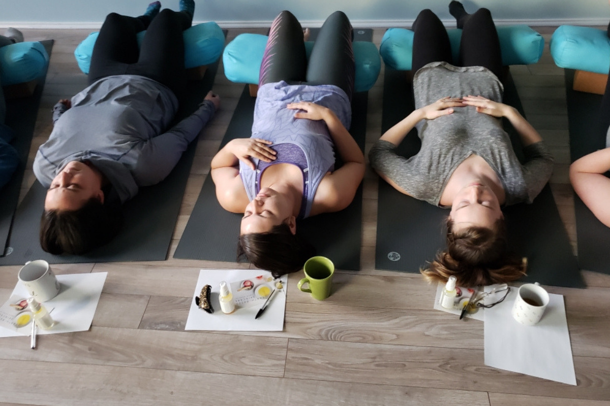 Women lying on yoga mats with their eyes closed
