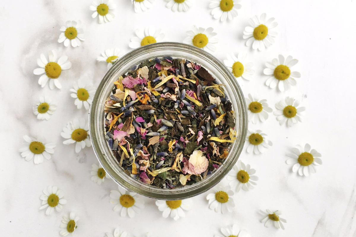Herbal steam jar surrounded by chamomile flowers