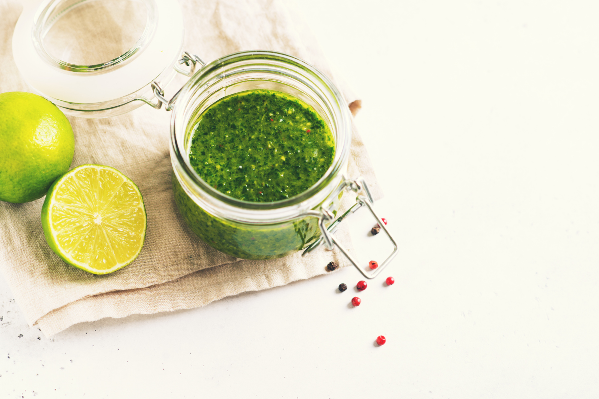 Chimichurri in small jar on white table