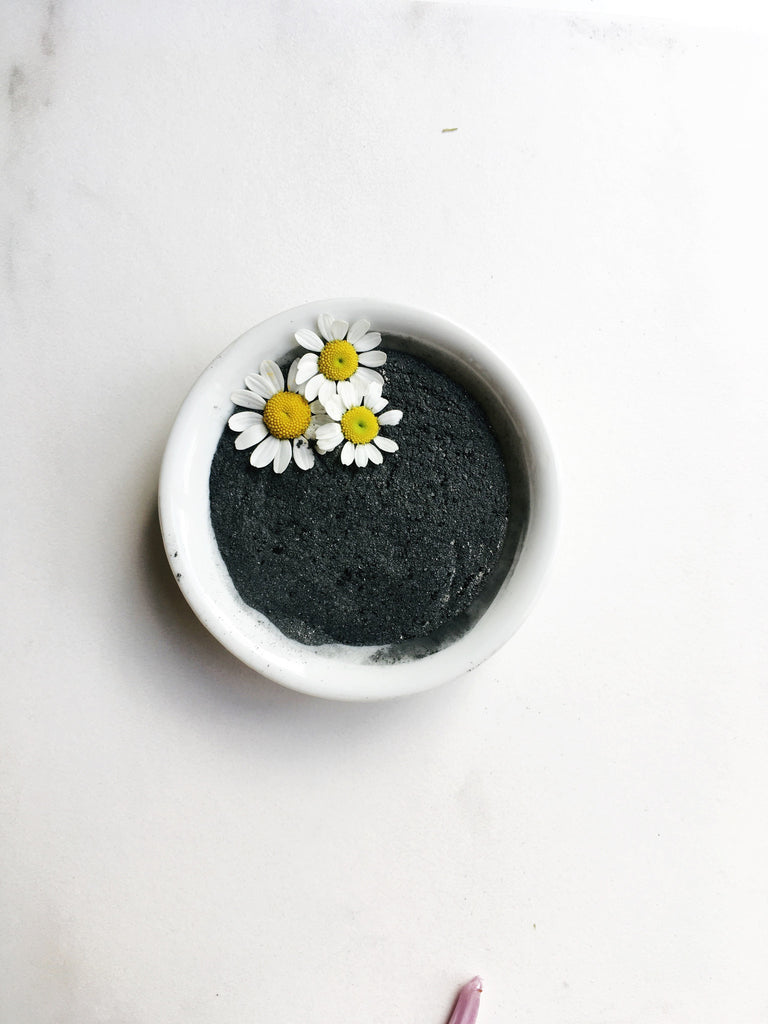 White dish of black herbal mask with chamomile flowers