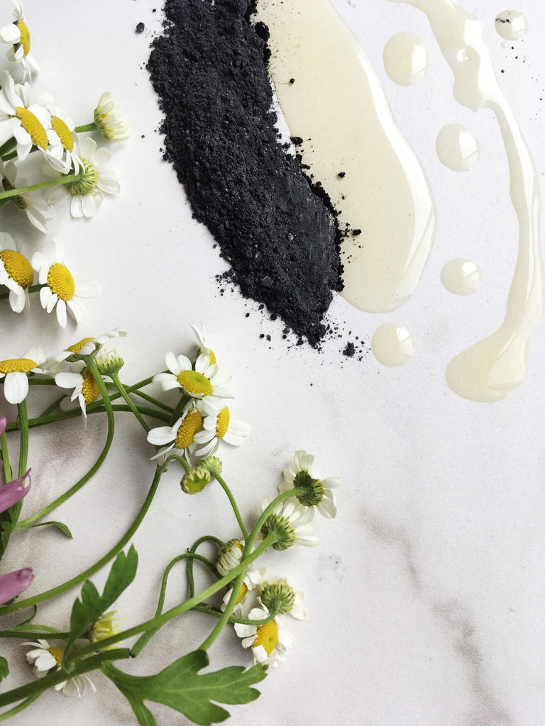 Black herbal mask and herbal oil mixing together on marble slab and chamomile flowers