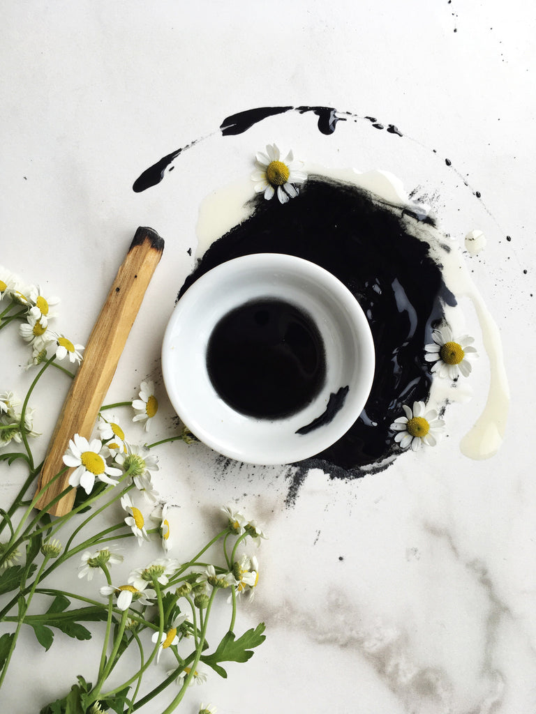 Black herbal mask in white dish on marble slab with chamomile flowers and palo santo incense