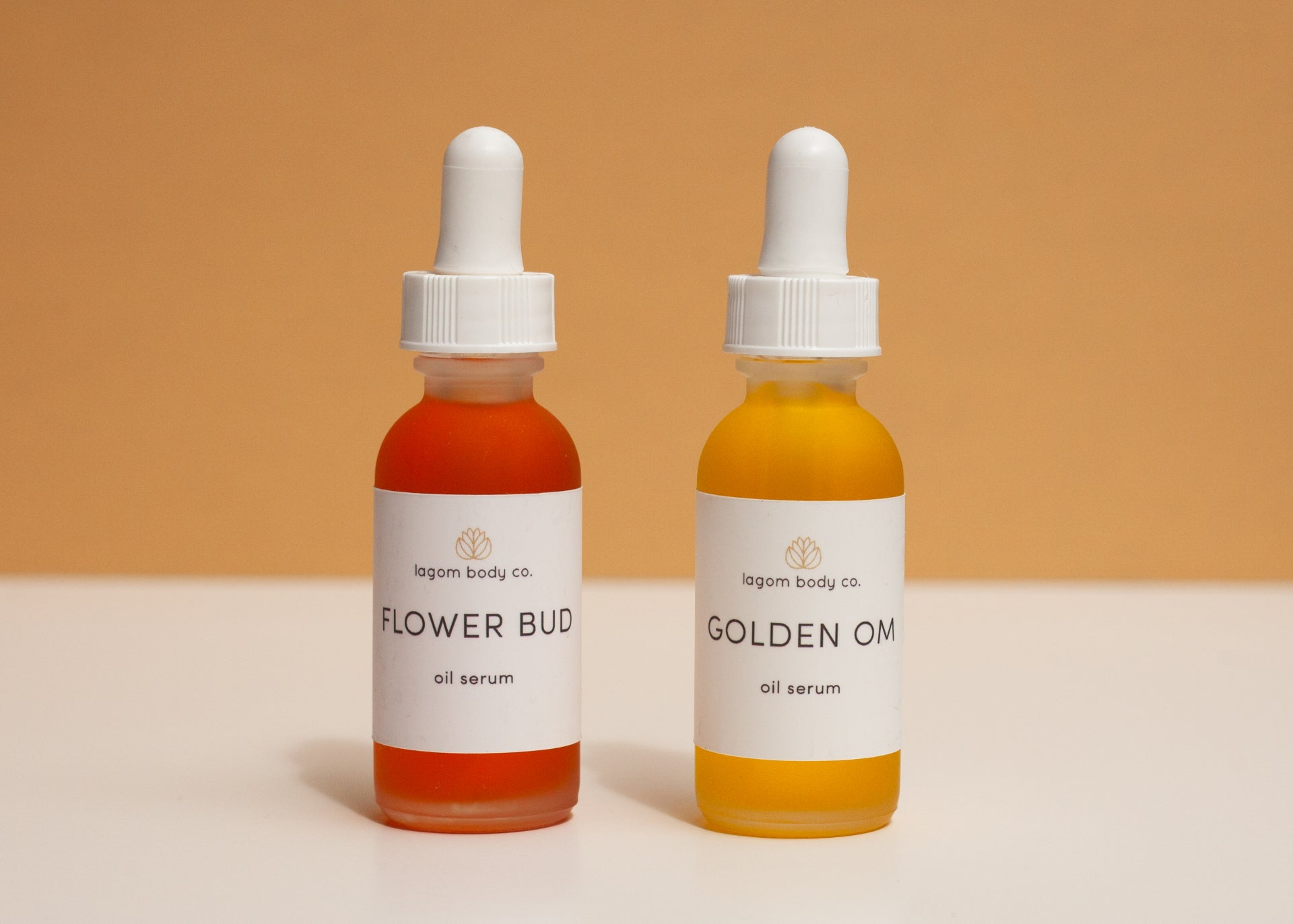 FLOWER BUD AND GOLDEN OM OIL SERUMS AGAINST GOLDEN BACKGROUND