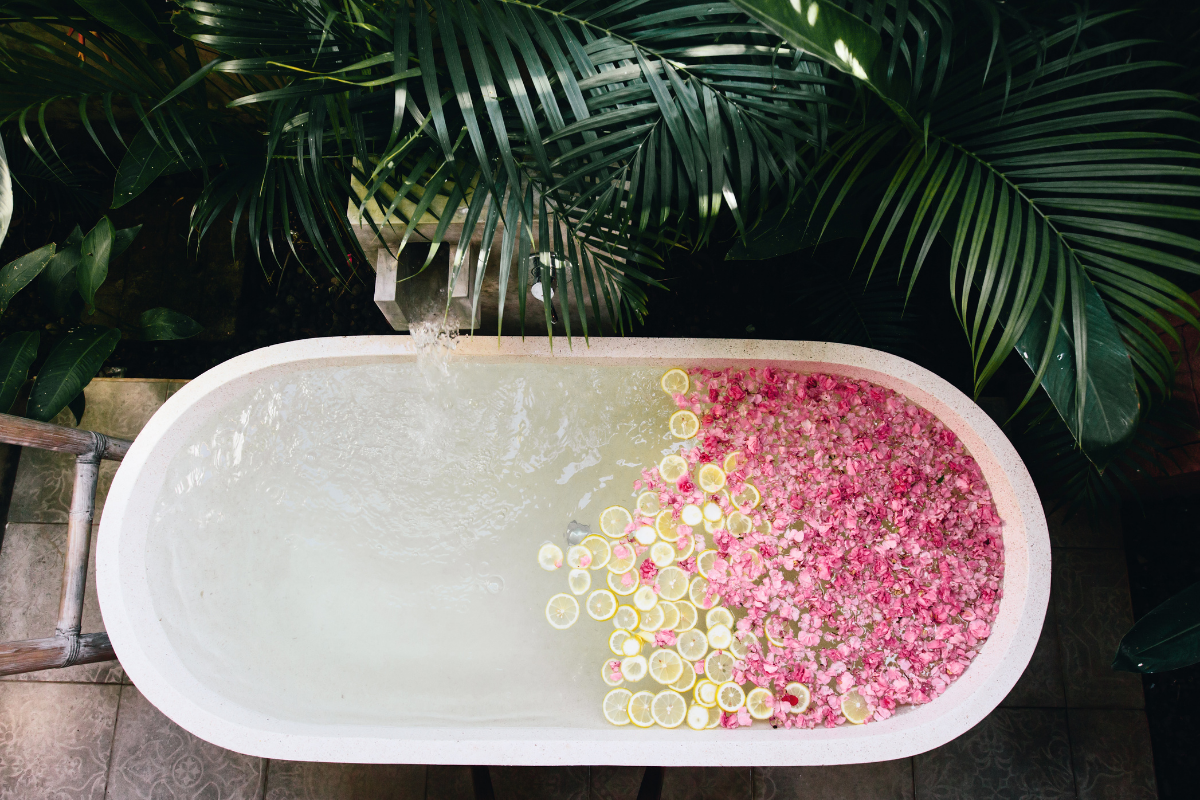 bath rub from above filled with rose petals and lemon
