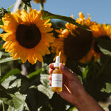 Someone holding Golden Om Illuminating Oil Serum against background with blue sky and blooming sunflowers