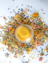 Restore Balm with lavender, rose, calendula petals on white marble table
