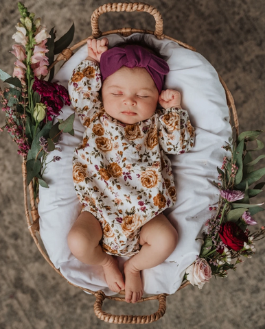 baby in bassinet with flowers