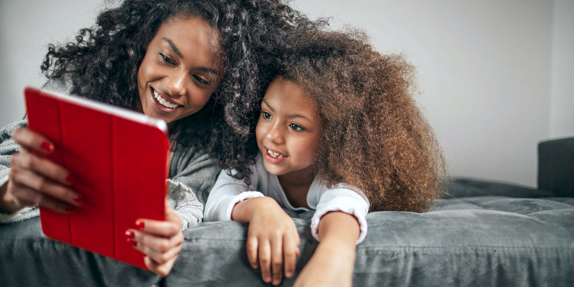 Mother and daughter on bed looking at a tablet
