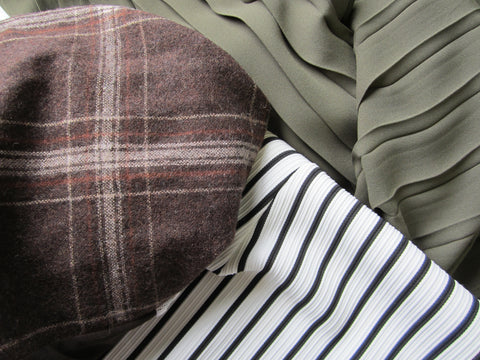 Brown wool plaid fabric, black and white stripe, forest green pleated chiffon fabric.