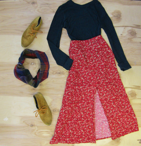 Flat lay: Red flower skirt pared with black long sleeve top, mustard colored shoes, and Regenerous Designs colorful plaid infinity scarf.