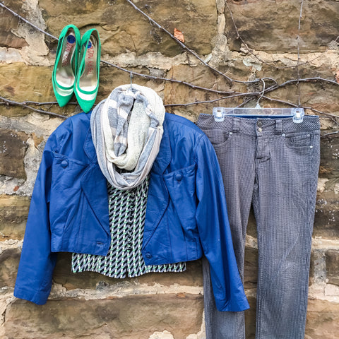 Flat lay: indigo leather jacket, black, white, and green checkered, button-down blouse, gray wash, striped jeans, green, pointed toe heels, and gray and white Regenerous Designs scarf.
