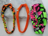 orange, yellow, and black buttonband beside an orange buttonband and a pink, green, and black big braided headband