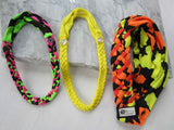 bright pink, green, and black buttonband beside yellow buttonband and an orange, yellow, and black big braided headband