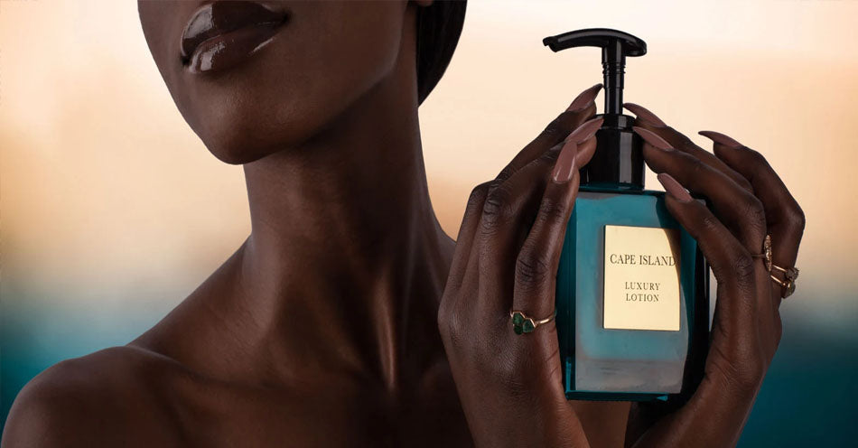 A woman holding a Cape Island luxury body lotion. Cape Island candles, body and bath products and home fragrances are available at Sarza home goods and furniture store in Rye New York