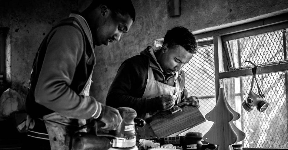 The Coco Africa team of artisans in their workshopcrafting their wooden home and kitchen products. Coco Africa wooden home décor products are available at Sarza home goods and furniture store in Rye New York