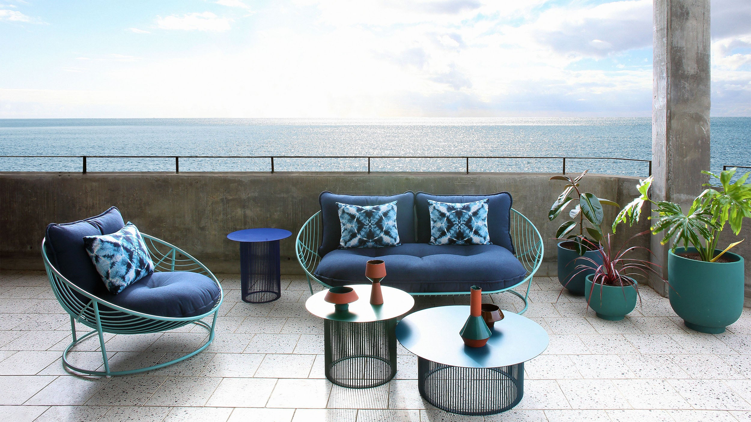 Haldane Martin, outdoor furniture, chairs and coffee tables styled in outdoor setting. Haldane Martin outdoor furniture is available at Sarza home goods and furniture store in Rye New York.