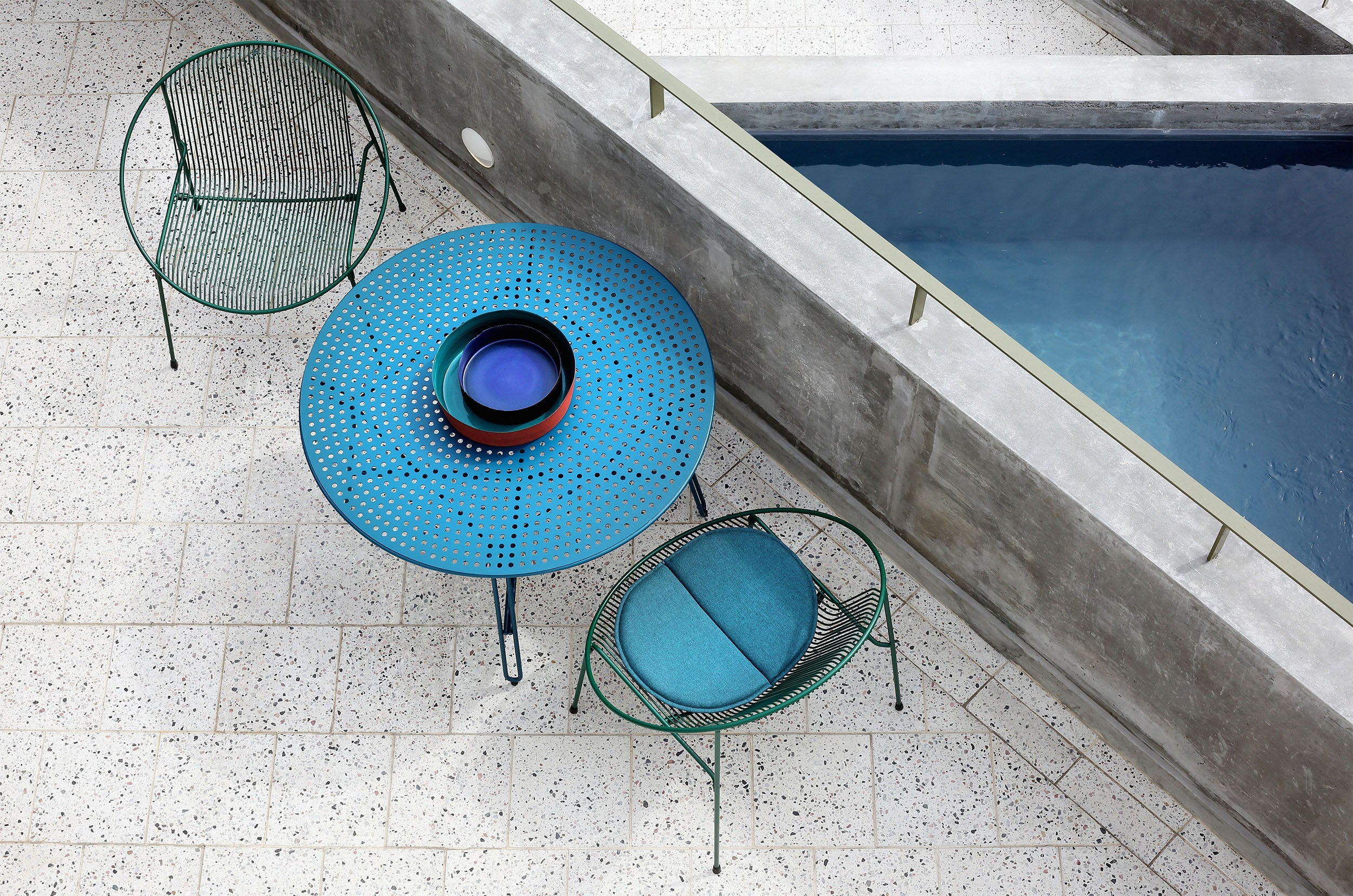 Haldane Martin, outdoor furniture, blue outdoor tables and chairs styled in an outdoor setting.  Haldane Martin outdoor furniture is available at Sarza home goods and furniture store in Rye New York.