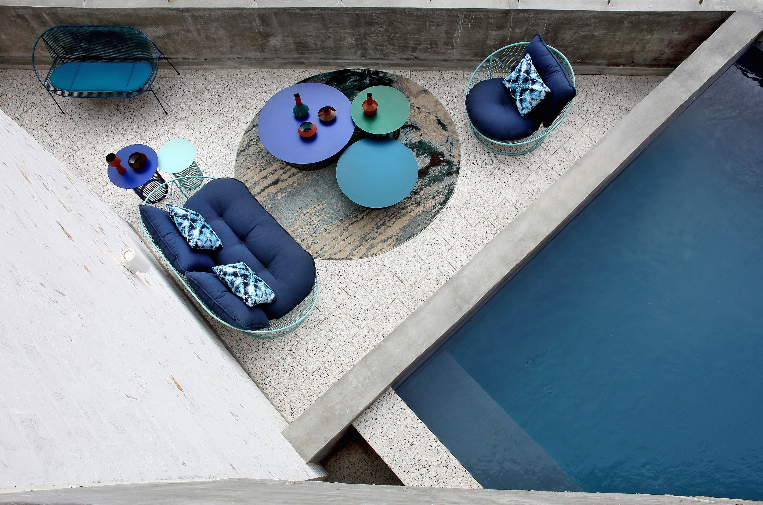 Haldane Martin outdoor furniture collection, green and blue outdoor chairs and coffee tables, styled in outdoor setting. Haldane Martin outdoor furniture is available at Sarza home goods and furniture store in Rye New York.