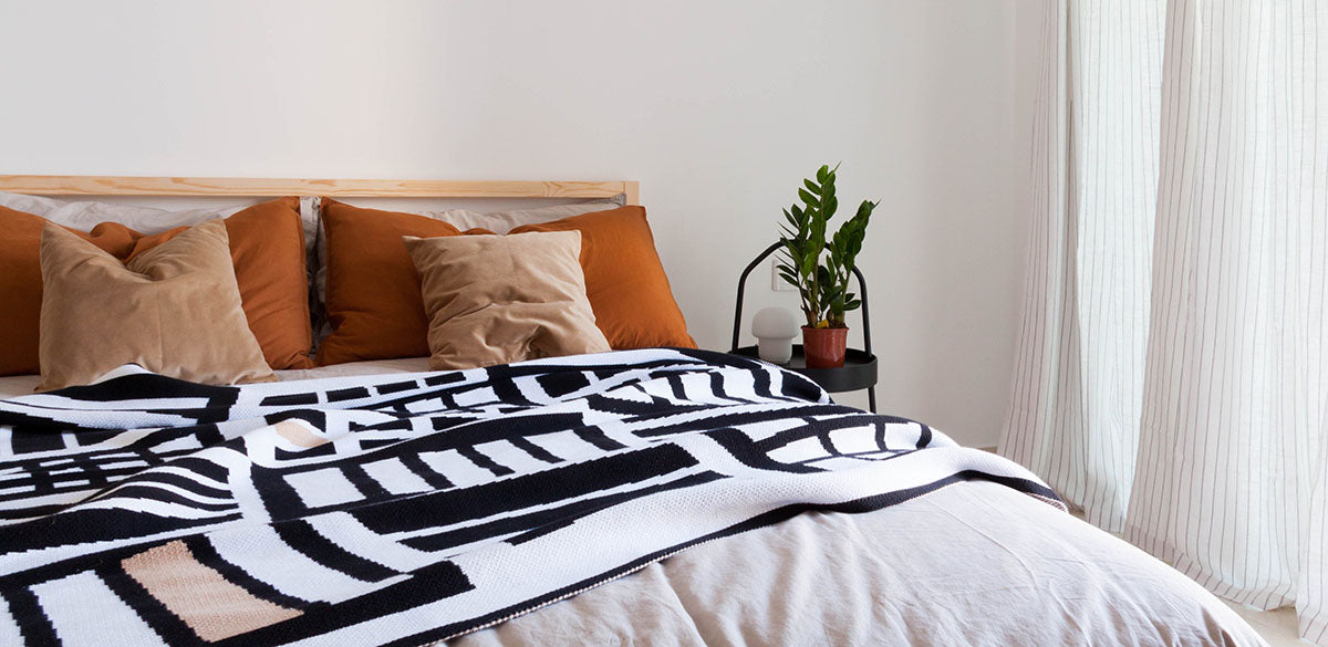 A Something Good Studio blanket styled on a bed.Something Good home décor products are available at Sarza home goods and furniture store in Rye New York.