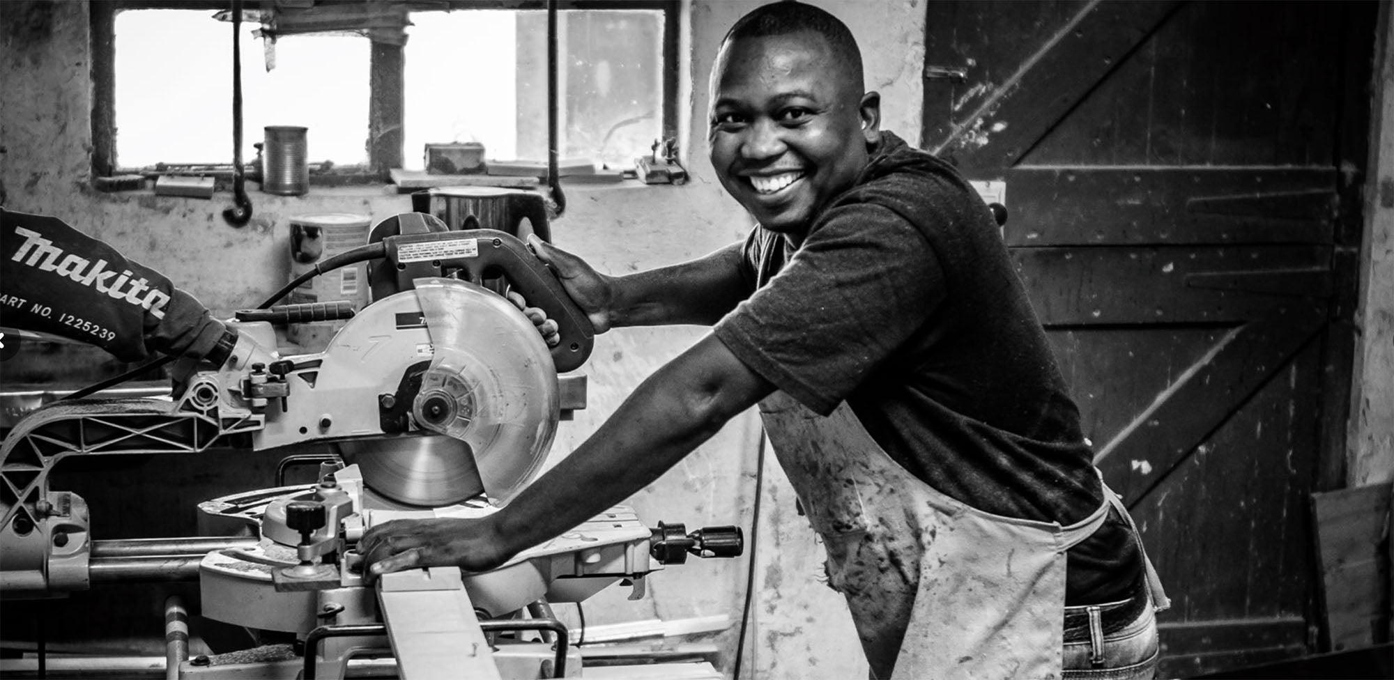A member of the Coco Africa team of artisans at work in the wood workshop, smiling to camera. Coco Africa wooden home décor products are available at Sarza home goods and furniture store in Rye New York