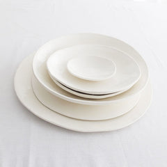Klomp Ceramics Everyday white range plates and bowls. The company makes handmade ceramic tableware. Available at Sarza home goods and furniture store in Rye New York.