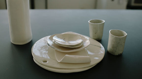 Klomp Ceramics platter, cups and bowls in white, marble and organic forms. The company makes handmade tableware. Available at Sarza home goods and furniture store in Rye New York.