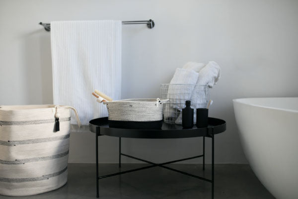 Mia Melange cotton baskets in black and white styled in a bathroom setting. Mia Melange products available at Sarza home goods and furniture store in Rye New York.