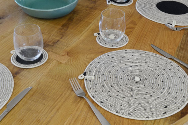 Mia Melange placemats in black and white, styled on a dining table. Mia Melange products available at Sarza home goods and furniture store in Rye New York.