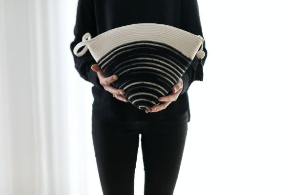 Mia Melange cotton bag in black and white being held. Mia Melange products available at Sarza home goods and furniture store in Rye New York