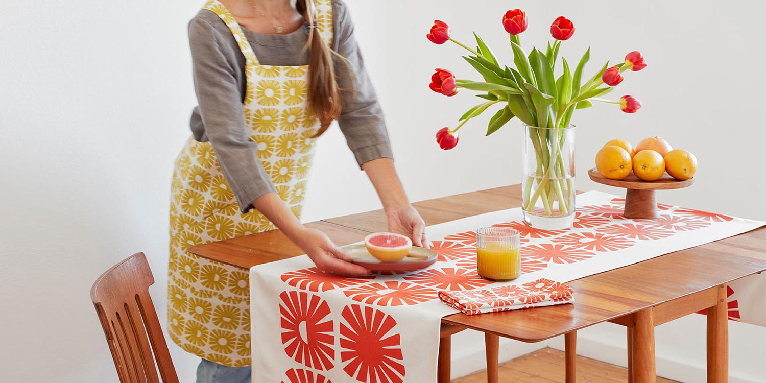 Skinny laMinx table runner, napkins and aprons styled on a tabletop. Skinny laMinx home décor products are available at Sarza home goods and furniture store in Rye New York.