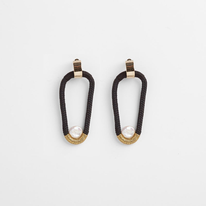 AMA EARRINGS - JEWELRY BY PICHULIK. These earrings reference the hero neckpiece Ama that celebrates the heroines of the collection-the Ama pearl divers of coastal towns of Japan. Black rope elegantly adorned with black and gold elliptical forms each framing a fresh-water form.
