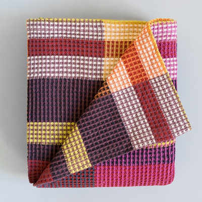 MAGENTA VROU VROU BLANKET by Mungo Design. A bold and robust cotton throw with zig zag and geometric patterns. The classic waffle weave has a cellular structure which gives the Vrou-Vrou a chunky body and texture. The pure cotton yarn ensures that it remains light and breathable, perfect for year round luxury.
