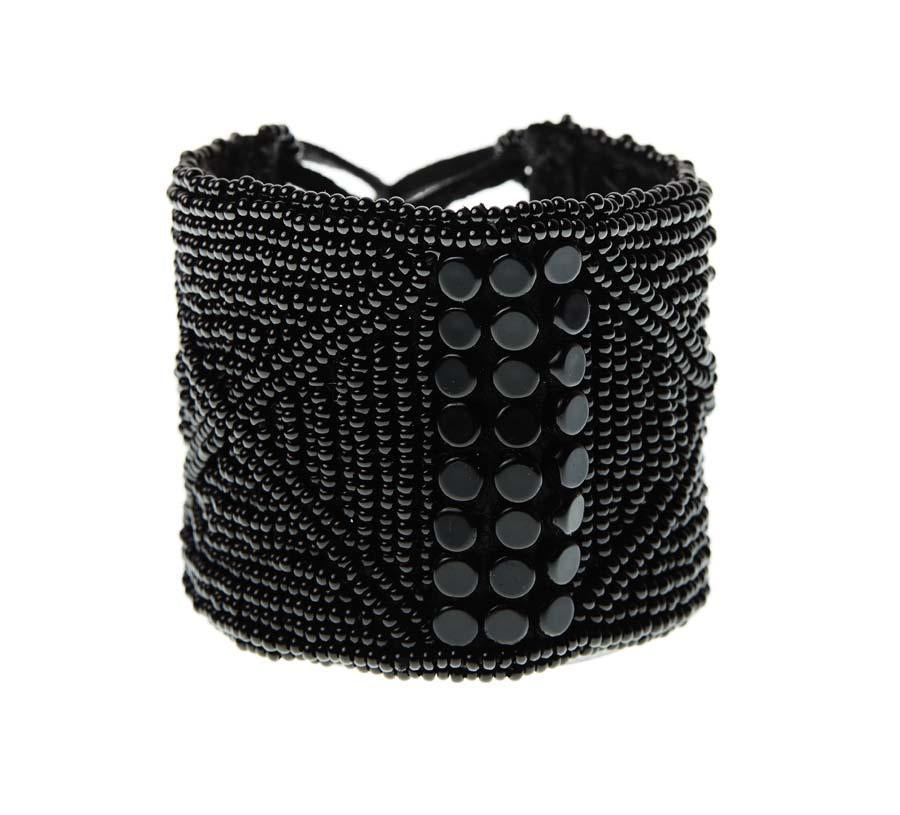 LEATHER BRACELET CUFF BY SIDAI DESIGNS JEWELRY. An intricately beaded leather bracelet from our Sipolio collection. This collection shares the journey of boyhood to warriorhood of a young Maasai male, who wears black and adorns himself with white beaded jewelry and detailed face markings.