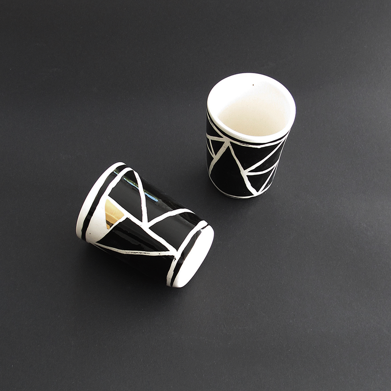 TRIANGLE RANGE CUP by Klomp Ceramics. A boldly decorated stoneware range with a unique triangle pattern and gold detailing. Black underglaze, clear glaze finish with gold lustre detail, unglazed underneath.
