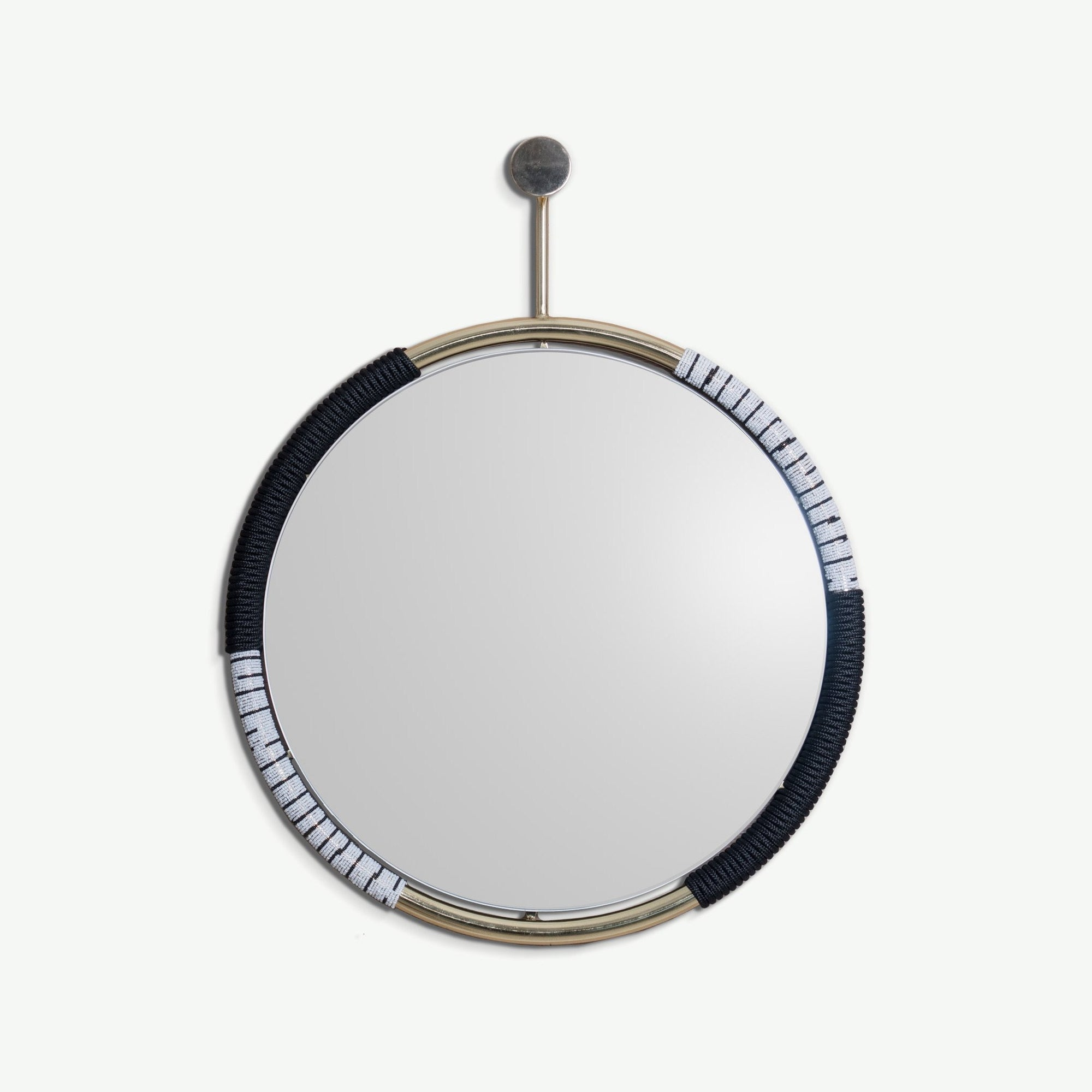 BUHLE MIRROR BRASS BY ARKIVIO. The Buhle Mirror crosses the boundaries of art and functional wall mirror. Its frame is hand wrapped with black rope and black & white beads & hangs from a matching wall hook.