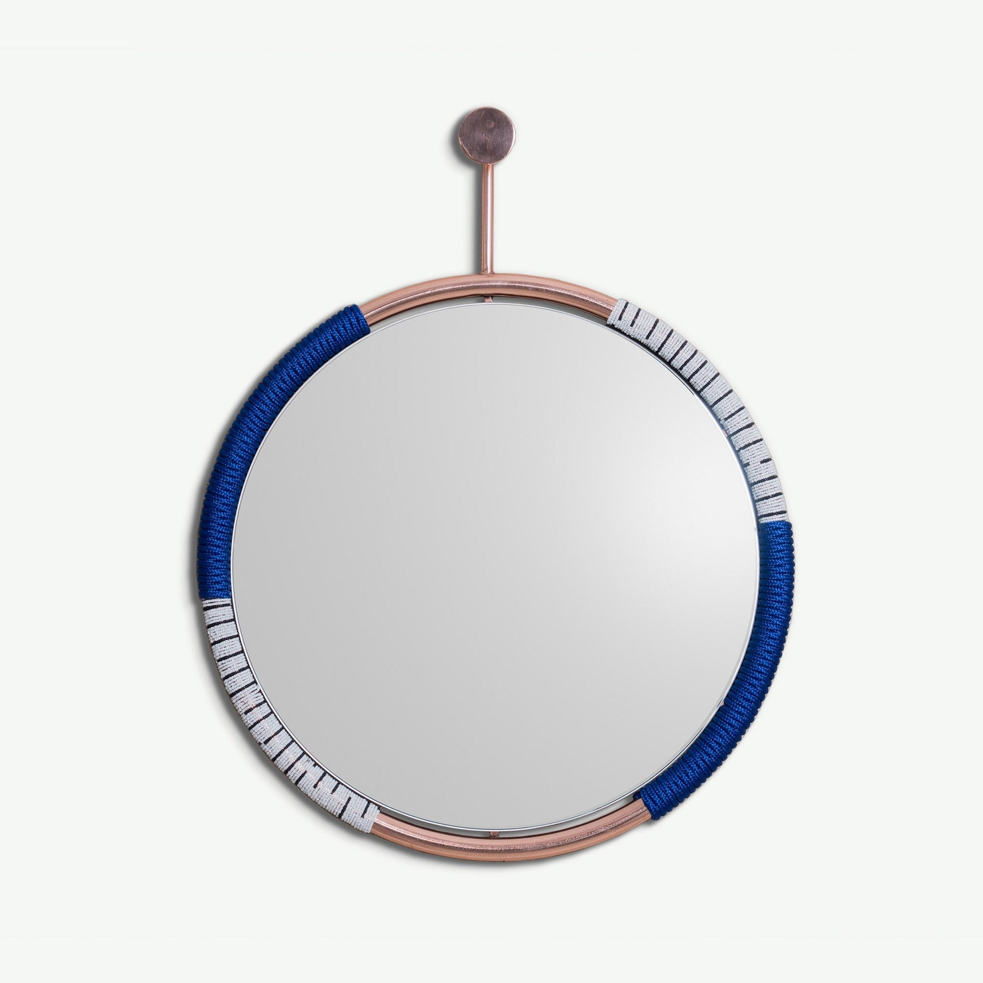 BUHLE MIRROR COPPER BY ARKIVIO. The Buhle Mirror crosses the boundaries of art and functional wall mirror. Its frame is hand wrapped with black rope and black & white beads & hangs from a matching wall hook.