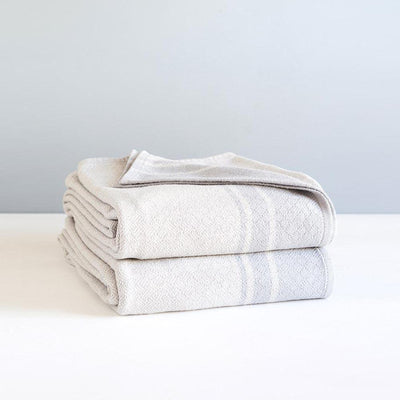FOSSIL QUILL BLANKET by Mungo Design. A pure cotton full-sized blanket with an intricate cross-hatched detail and bold border. Available in 3 beautiful colorways. Designed and woven in South Africa.