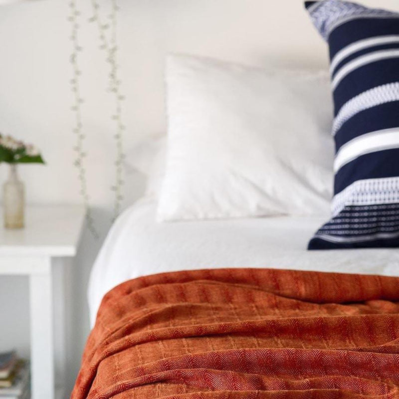 NAMIB ORANGE CHENILLE HERRINGBONE THROW by Mungo Design. The intricate design of the classic herringbone weave and the velvety texture of the chenille yarn gives this throw a luxurious tactile quality.