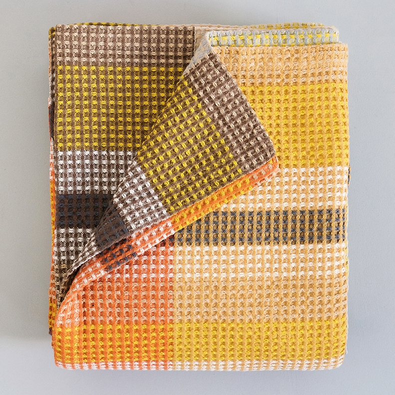 TAMARIND VROU VROU BLANKET by Mungo Design. A bold and robust cotton throw with zig zag and geometric patterns. The classic waffle weave has a cellular structure which gives the Vrou-Vrou a chunky body and texture. The pure cotton yarn ensures that it remains light and breathable, perfect for year round luxury.