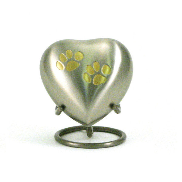 Pewter pet cremation keepsake with 2 paw prints. Heart shaped. 3 cubic inches of storage. Engraving available. OneWorld Memorials.